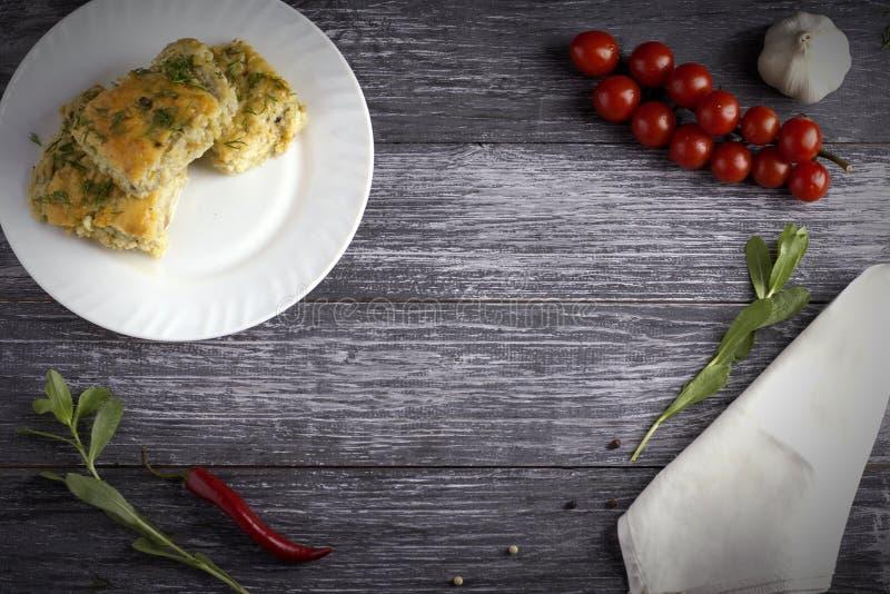 夏南瓜、米和乳酪可口自创砂锅在一块白色板材在木背景 库存照片