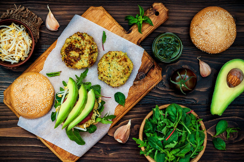 夏南瓜奎奴亚藜素食者汉堡用pesto调味汁和新芽 顶视图,顶上,平的位置 免版税库存照片