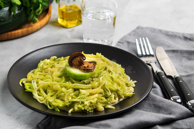 夏南瓜面条或Zoodles用乳脂状的蘑菇和Pesto调味汁 库存照片