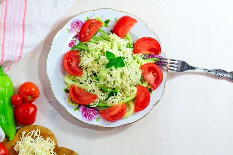 夏南瓜面条用在白色木桌上的乳酪 库存图片