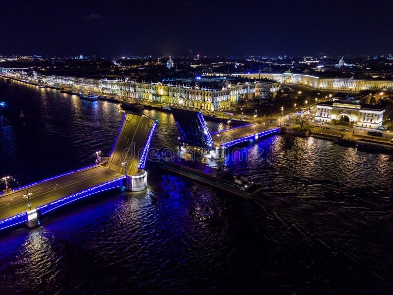 夏夜,圣彼德堡,俄罗斯 Neva河 船通过在拉长的平衡装置可移动的宫殿桥梁下 俄国 图库摄影