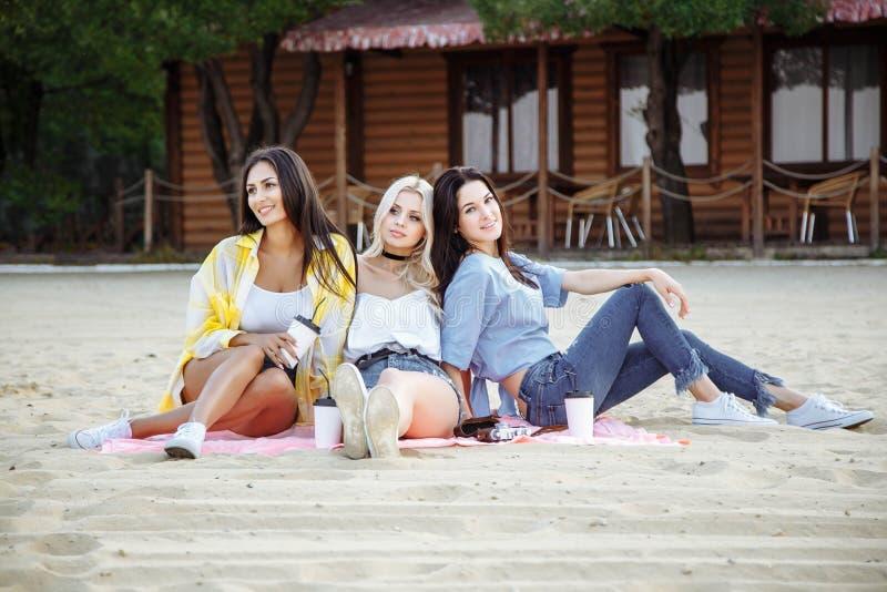 夏天、假日、假期和幸福概念-小组海滩的年轻可爱的妇女朋友 库存图片