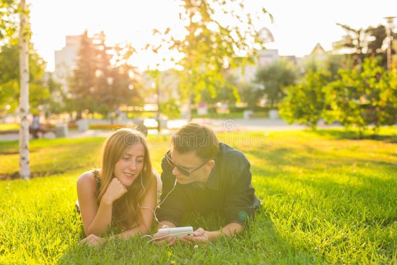 夏天、爱和人概念-接近说谎在与耳机的草和听到音乐的愉快的少年夫妇 免版税库存照片