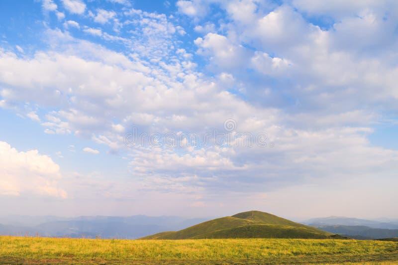 夏天与云彩的山风景在天空 免版税库存照片