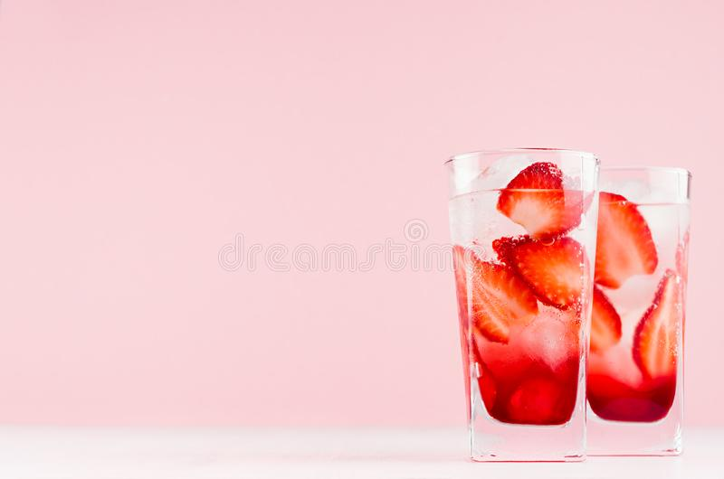 夏天与冰块、切片莓果、苏打在典雅的粉红彩笔墙壁上和白色木桌,拷贝空间的草莓柠檬水 免版税图库摄影