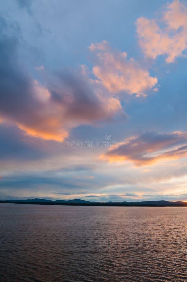夏天与剧烈的云彩的日落风景-起了波纹日落夏天光点燃的水表面 图库摄影