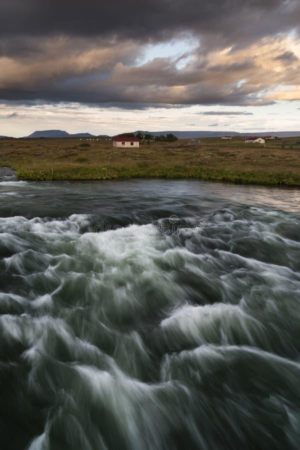 夏天与发怒的河的冰岛风景阴暗天气的 库存照片