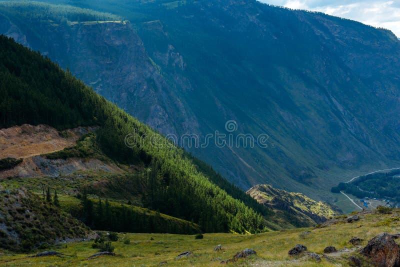 夏天与绿色树的山风景在倾斜和曲线路在岩石的脚 从草甸的壮观的看法 图库摄影