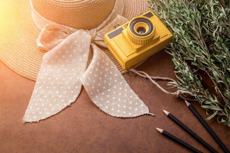 夏天与黄色玩具照相机的旅行概念用妇女帽子麸皮 图库摄影