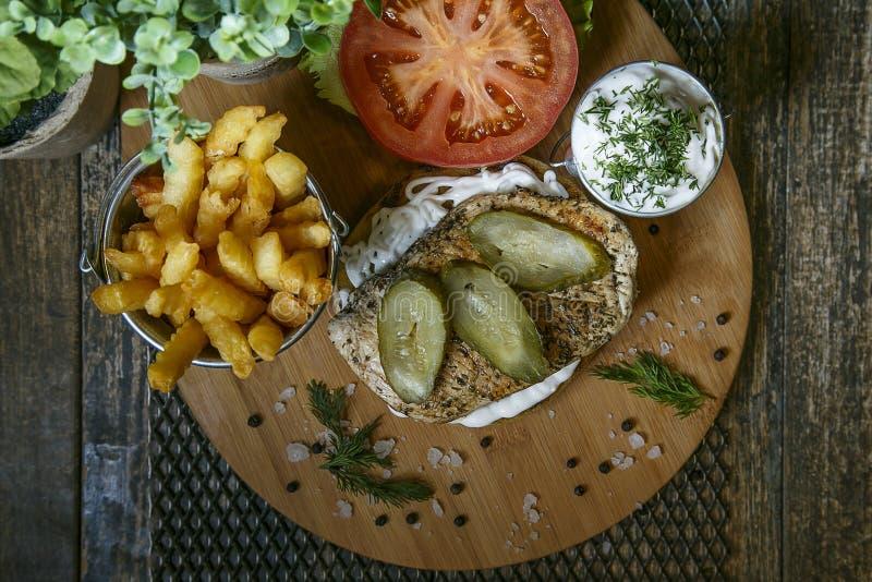 夏天乳酪汉堡用蕃茄和牛奶调味汁 免版税库存照片