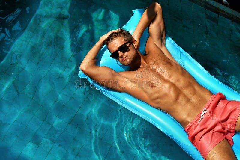 夏天人身体关心 美好男性放松在水池 库存照片