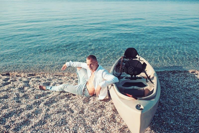 夏天休假和海洋旅行 享受在沙子的强壮男子的人夏日 海水的性感的人在小船附近 人放松  免版税图库摄影