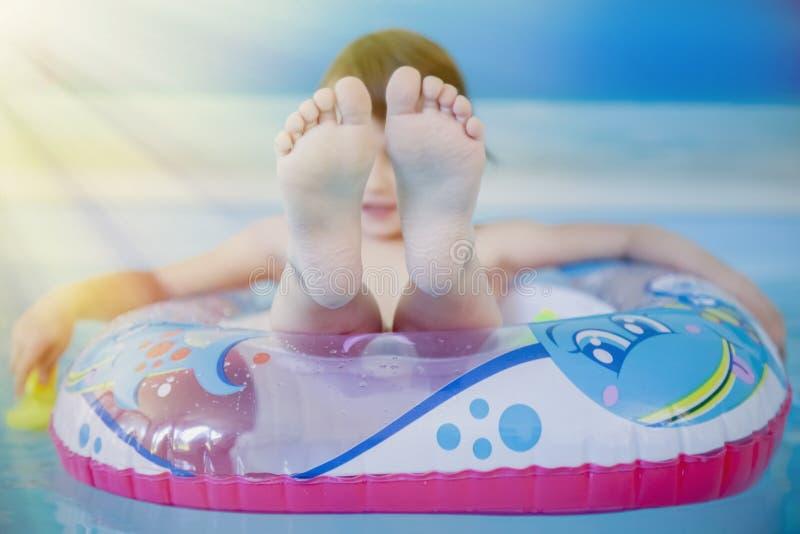 夏天休假来临 使用在与五颜六色的儿童小船的水中的愉快的小孩女孩 免版税图库摄影
