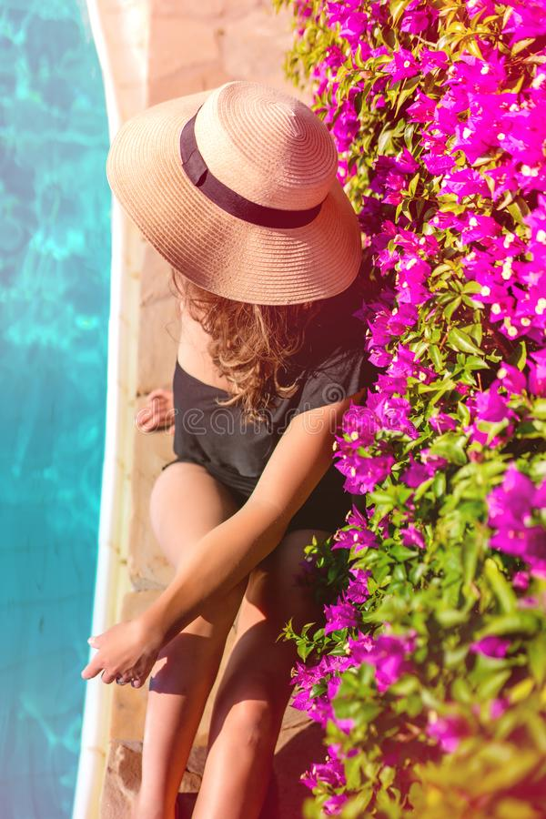 夏天休假-放松在游泳场、游泳池边有草帽的和太阳镜附近的被晒黑的白种人妇女 免版税库存照片