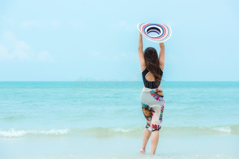 夏天休假 生活方式拿着大白色帽子和佩带比基尼泳装时尚夏天旅行的妇女冷颤走在含沙海洋bea 库存照片