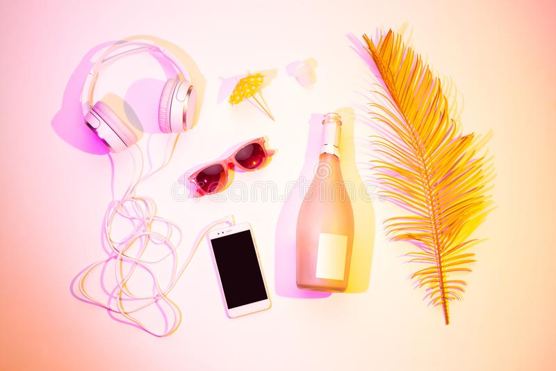 夏天休闲-耳机智能手机,香槟 免版税库存图片