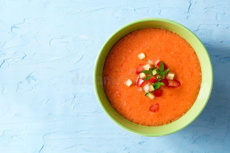 夏天冷的汤gazpacho用荷兰芹和菜在蓝色具体背景 免版税库存照片