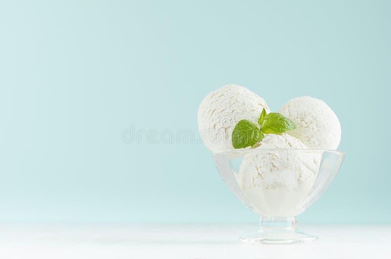 夏天冷的点心-在典雅的玻璃碗的三个乳脂状的冰淇淋球用在白色木桌和淡色蓝色墙壁上的绿色薄菏 免版税库存图片