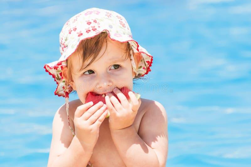 夏天吃西瓜的女婴 免版税库存照片
