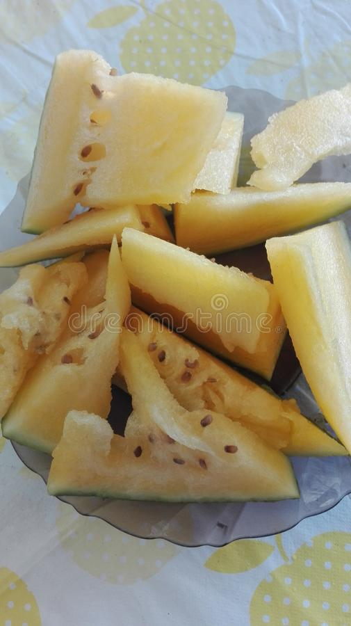夏天味道-黄色西瓜片断在一块板材的在白黄色桌布盖的桌上 库存照片
