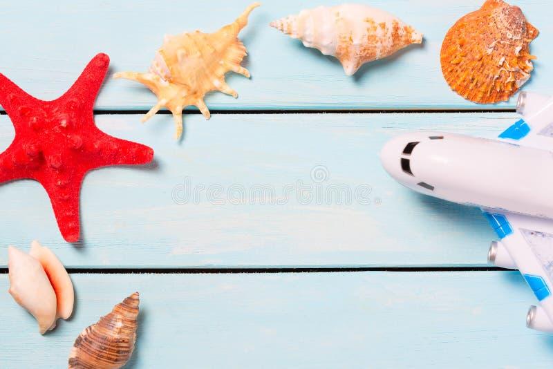 夏天和假期的概念 与玩具飞机的海壳和海星或者浅兰的木桌 您的文本的空位 库存照片