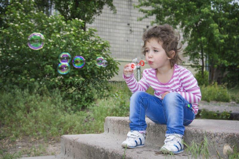 夏天在公园坐小女孩和b的步 库存照片