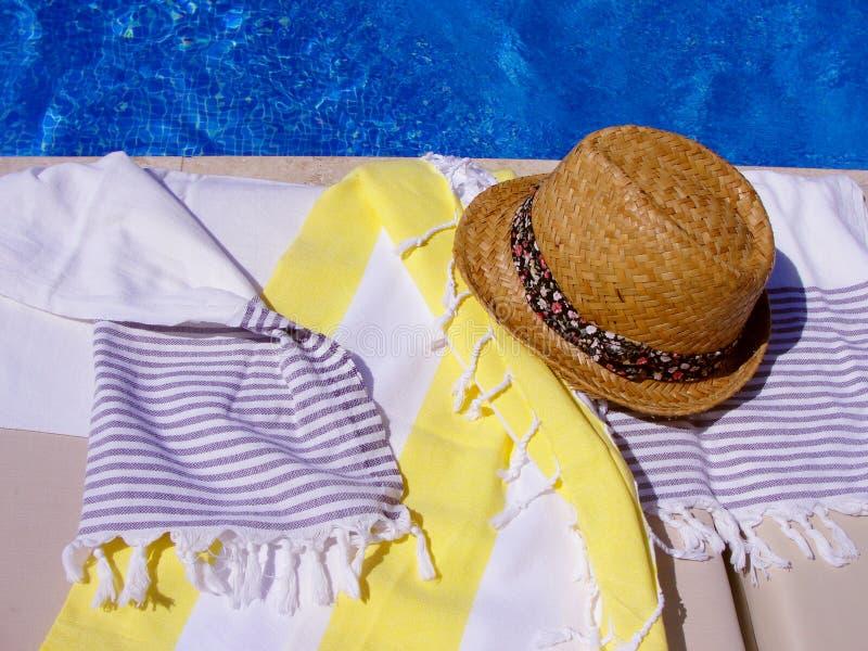 夏天在游泳场附近的草帽和棉花毛巾 图库摄影