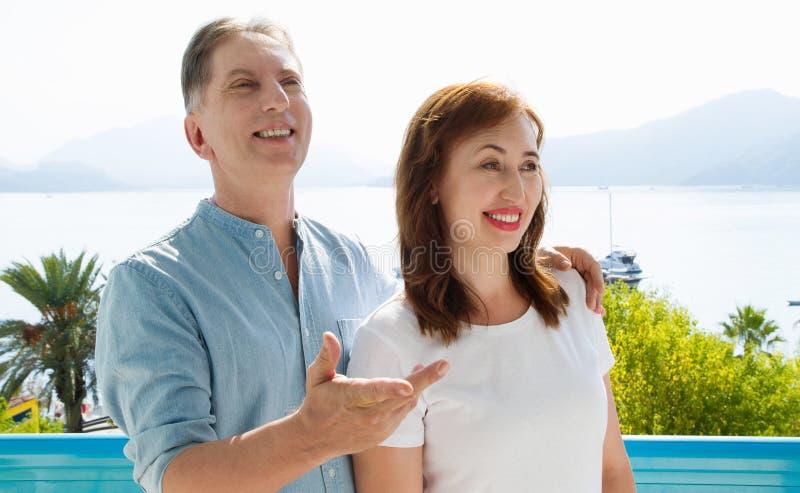 夏天在热带海滩的乐趣周末 在自然海背景的愉快的中间年迈的家庭夫妇 健康关系和爱 图库摄影