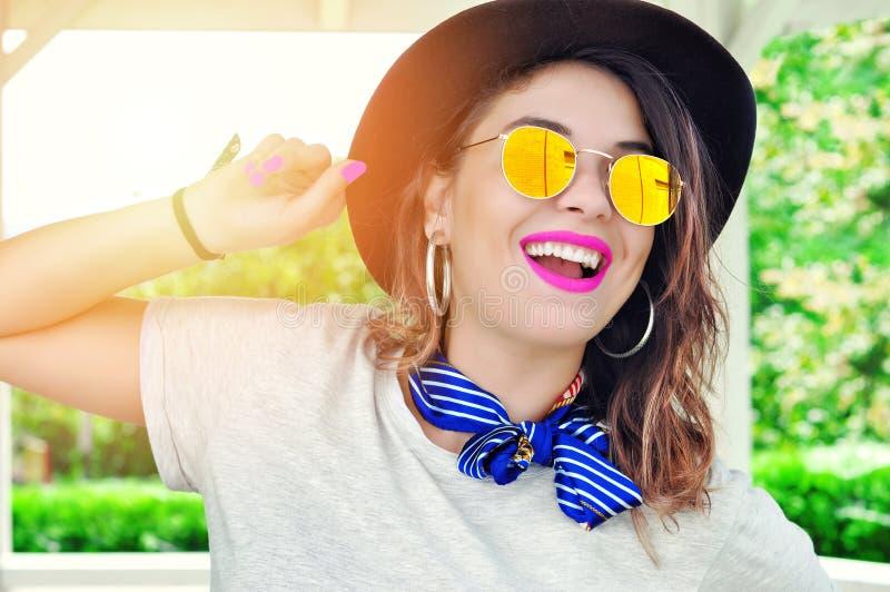 夏天城市震动 晴朗的生活方式时尚画象相当年轻微笑的妇女粉色口红 免版税库存照片