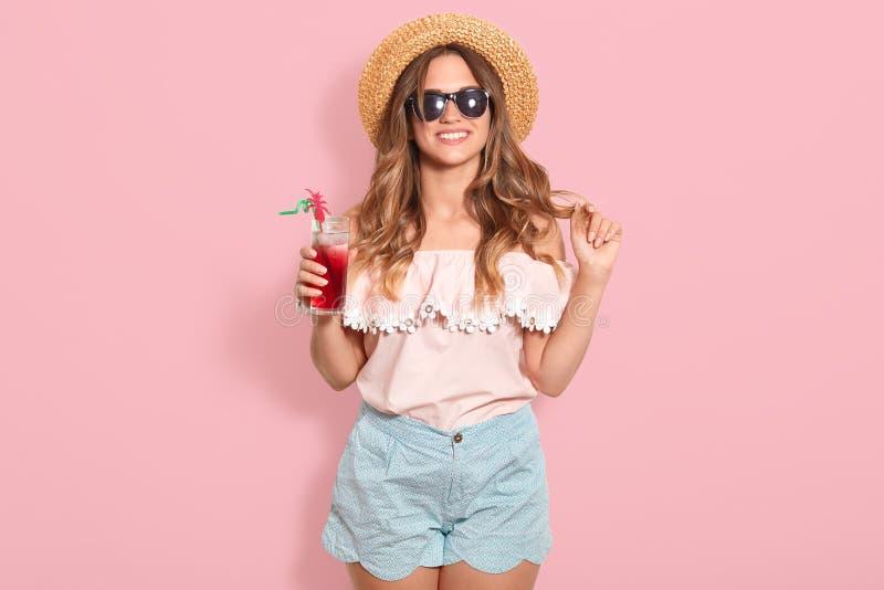 夏天女衬衫、蓝色短小、黑拿着与冷的饮料一会儿的太阳镜和草帽的美丽的年轻女人玻璃 库存照片