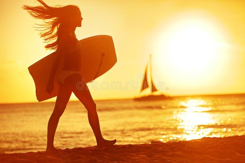夏天妇女身体冲浪者在日落的海滩乐趣 库存图片