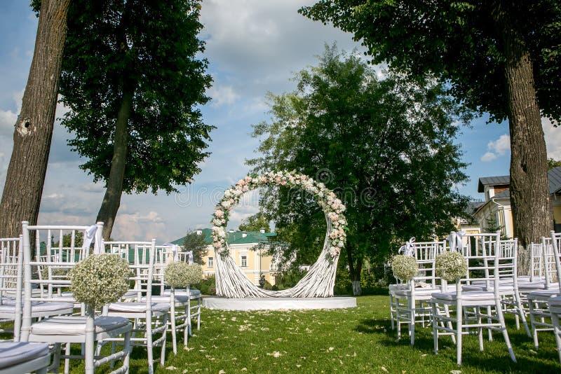 夏天室外婚礼装饰 分支美丽的白色白玫瑰、八仙花属和麦曲拱和花束  免版税库存照片