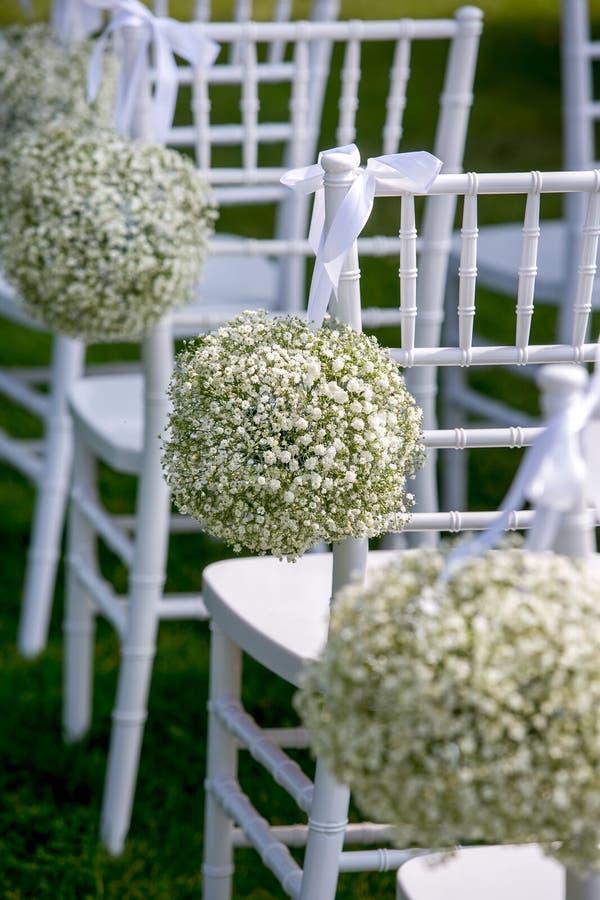 夏天室外婚礼装饰 用麦球装饰的白色椅子,垂直的看法 库存照片
