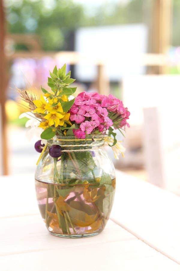 夏天小美丽的花束在桌上的一个花瓶开花 构成 免版税图库摄影