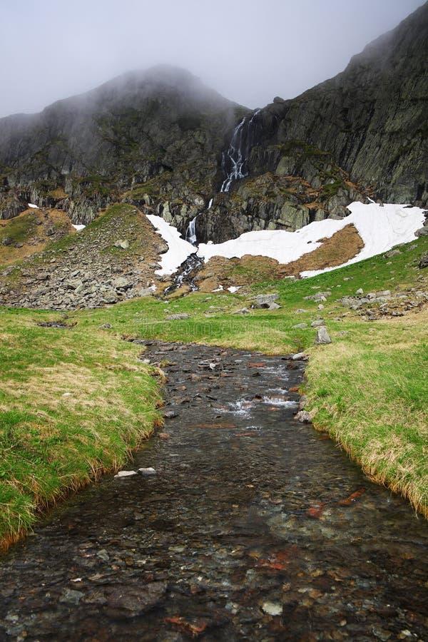 夏天山风景在Transylvanian阿尔卑斯,有有薄雾的多雨云彩和瀑布的 图库摄影