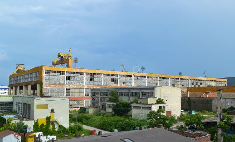 夏天工业风景:蓝天和一个大被放弃的工业黄色大厦与残破的窗口 免版税库存图片
