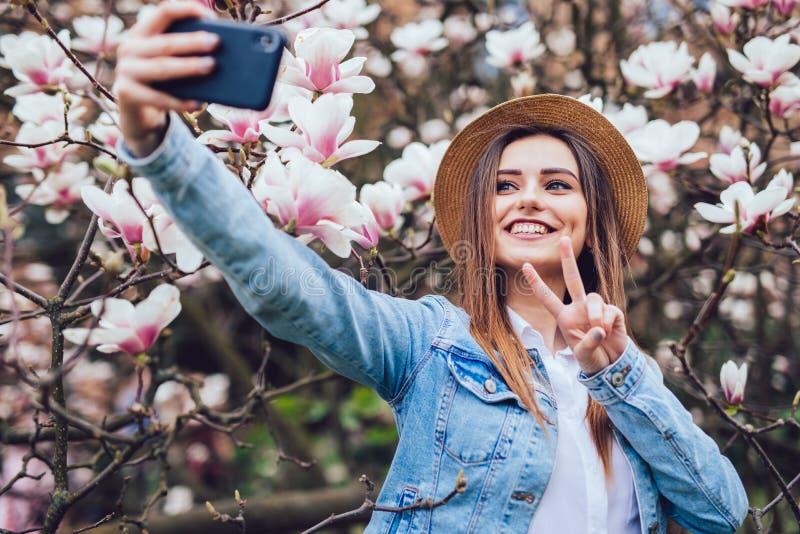 夏天帽子作为selfie的年轻秀丽妇女在开花木兰树附近的电话在晴朗的春日 免版税库存照片