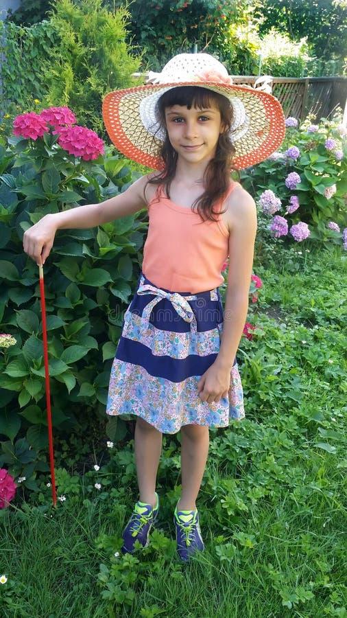 夏天帽子的女孩在开花的八仙花属的灌木附近在季节性别墅的站立 免版税图库摄影