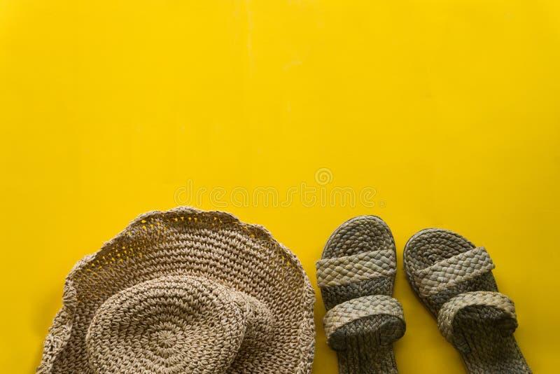 夏天帽子织法和凉鞋织法有黄色背景 库存照片