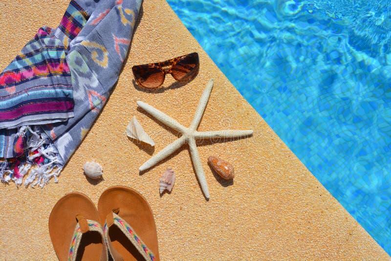 夏天平的位置,由游泳池边的cothes, 免版税库存图片