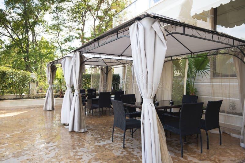 夏天庭院撤退 树荫处帐篷在休息的中心的疆土与咖啡桌和椅子的 免版税库存图片