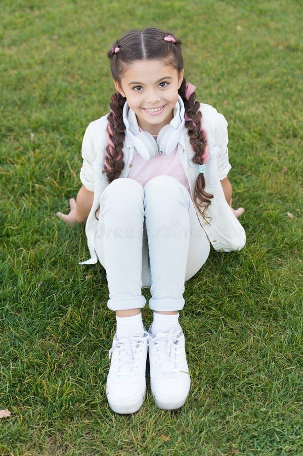 夏天意味幸福时光和好阳光 享受暑假的小孩子 放松在绿草的女孩  库存图片