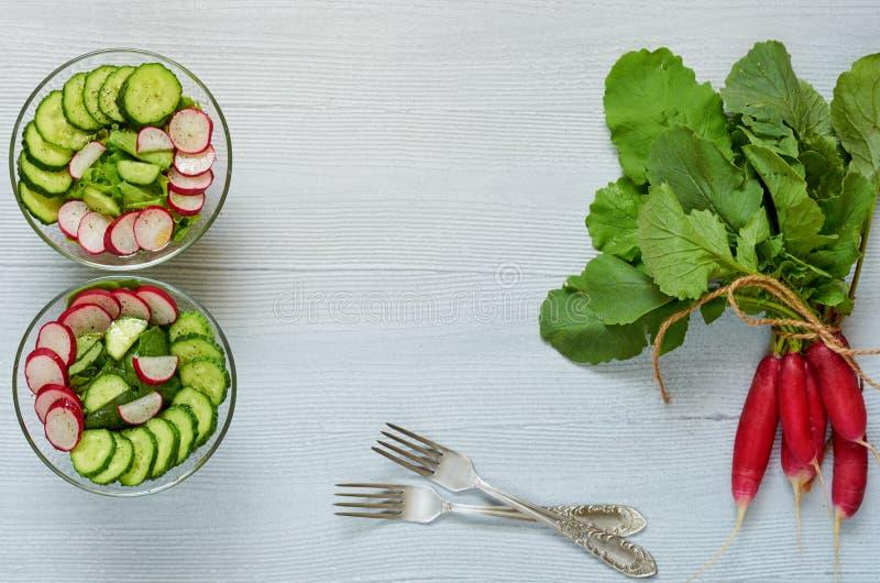 夏天戒毒所沙拉用萝卜、黄瓜和菠菜在玻璃碗在灰色厨房用桌上与拷贝空间在中心 库存照片
