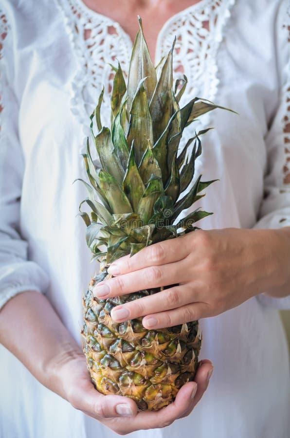 夏天拿着一个成熟菠萝的鞋带礼服的妇女 库存图片