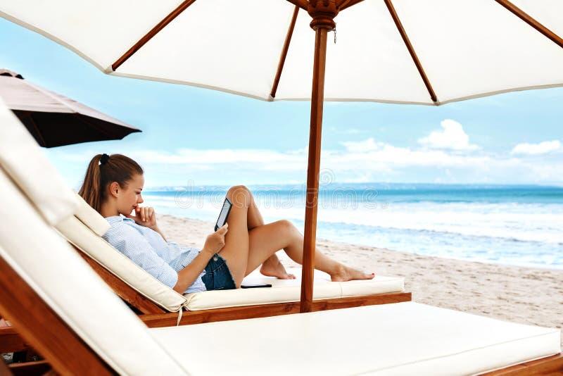 夏天放松 妇女读书,放松在海滩 夏令时 免版税库存图片