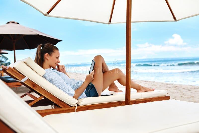 夏天放松 妇女读书,放松在海滩 夏令时 免版税库存照片