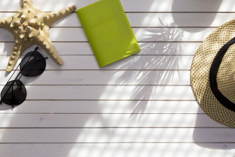 夏天旅行辅助部件在白色木背景平展放置 护照、帽子、太阳镜和海星妇女的夏天休假 免版税库存照片