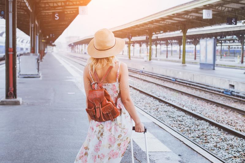 夏天旅行,带着等待她的火车的手提箱的妇女 免版税库存照片