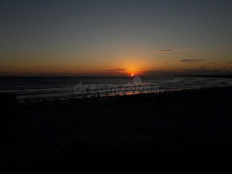 夏天日落照片在Arraial做Cabo -与人的黄昏海滩沙子的 免版税库存照片