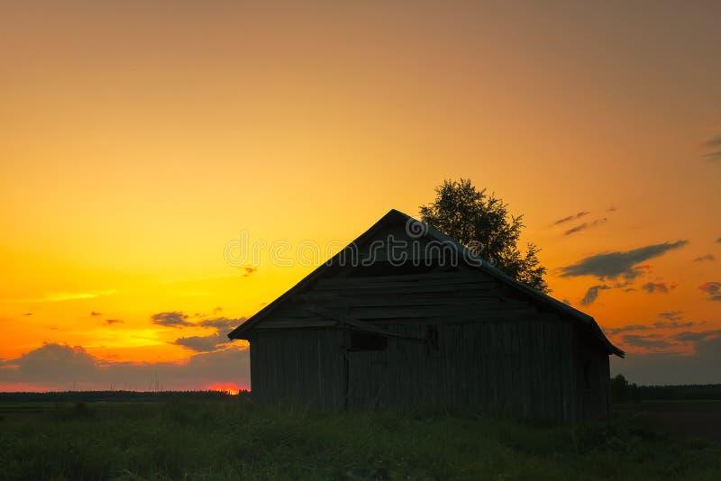 夏天日落的偏僻的谷仓议院 免版税库存图片